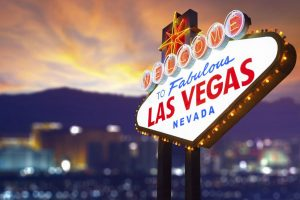 Welcome to Las Vegas sign with unfocused city lights. Just Fly Business can take you there with business class flights to Las Vegas