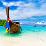 Phuket Longboat in calm blue seas - Your Next First Class Destination | Just Fly Business