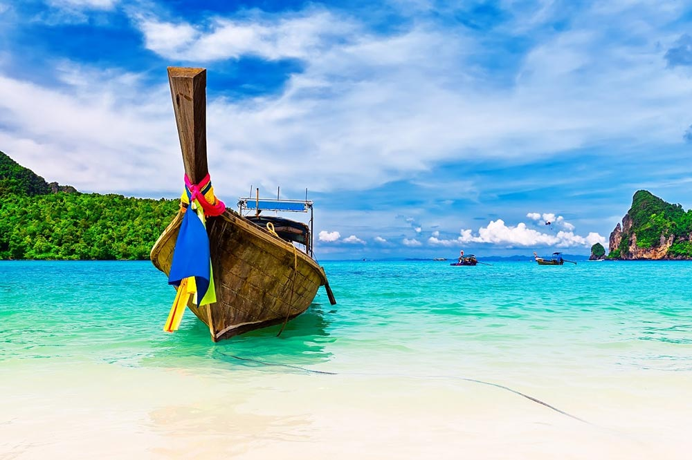 Phuket Longboat in calm blue seas - Your Next First Class Destination   Just Fly Business