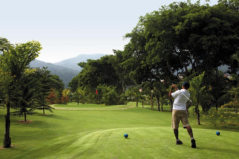 Man Teeing Off at the golf course at Shangri-La's Sayang Resort & Spa in Penang