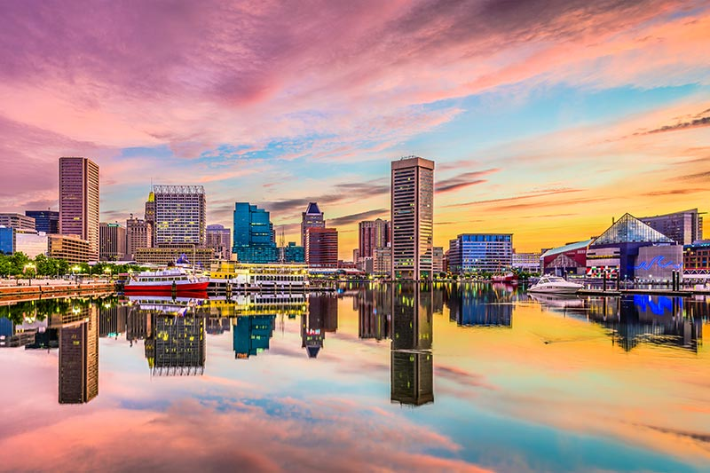 Baltimore city skyline reflecting in teh water of the Inner Harbour at sunset