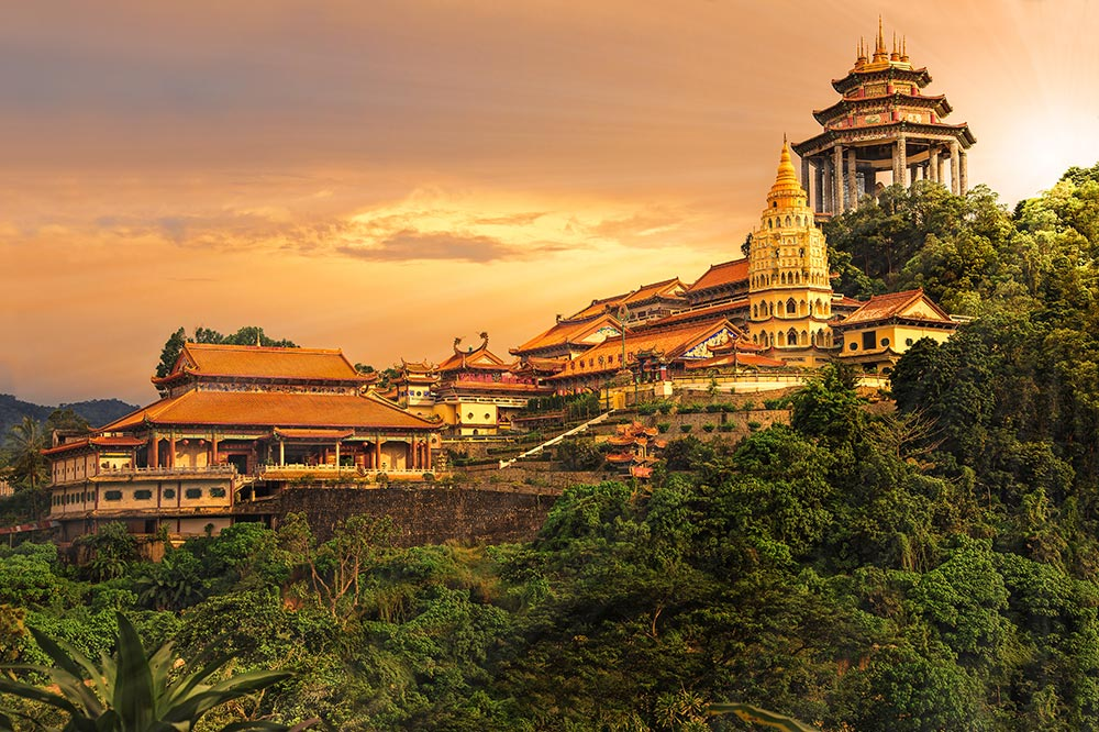 Kek Lok Si Temple at sunset surrounded by rainforest in Penang