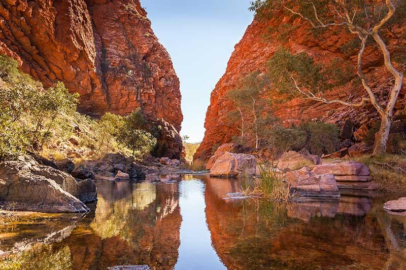 Red rock cliffs surrounding a natural billabong near Alice Springs.