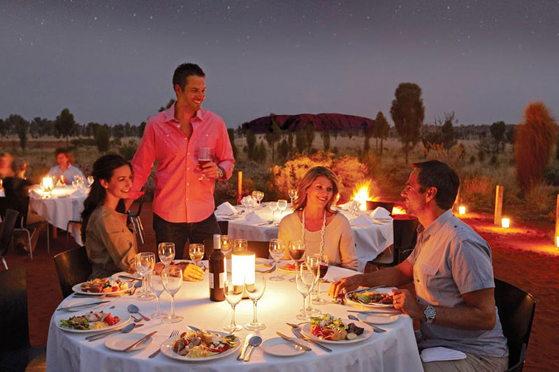 People dining by candlelight in Australia's Outback with Uluru in the background.