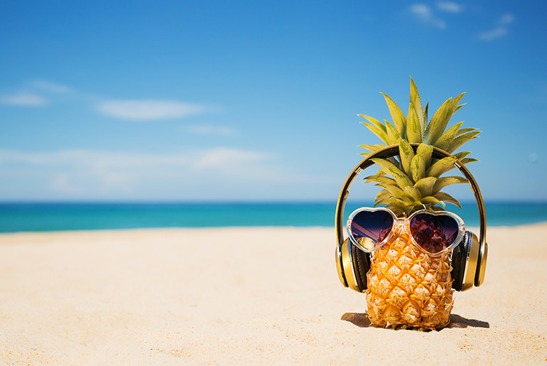 Pineapple wearing headphones on beach - Just Fly Business