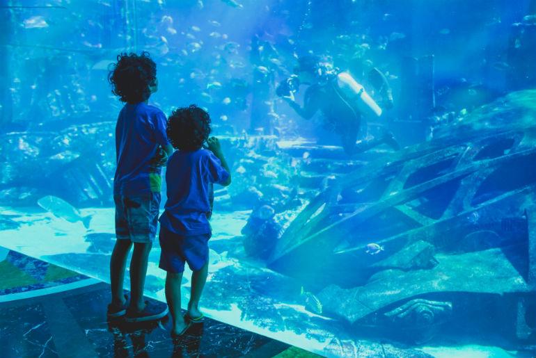 Silhouettes kids in big Dubai aquarium