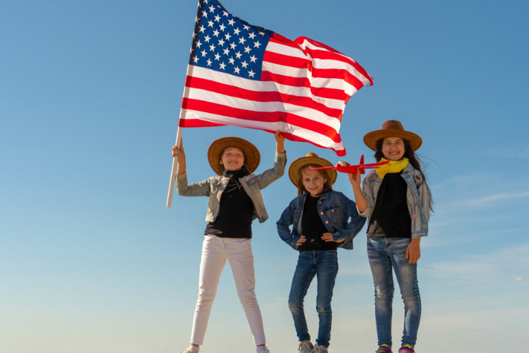 Three girls in cowboy hats with the American flag