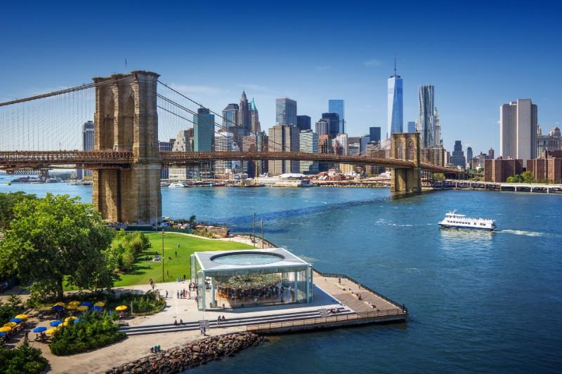 Ferry under Brooklyn Bridge in New York USA