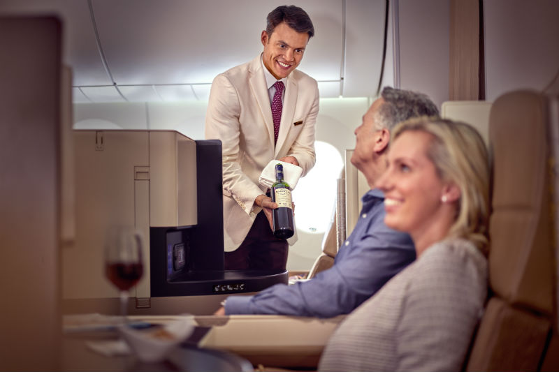 two passengers are served wine in a Etihad Business Class cabin
