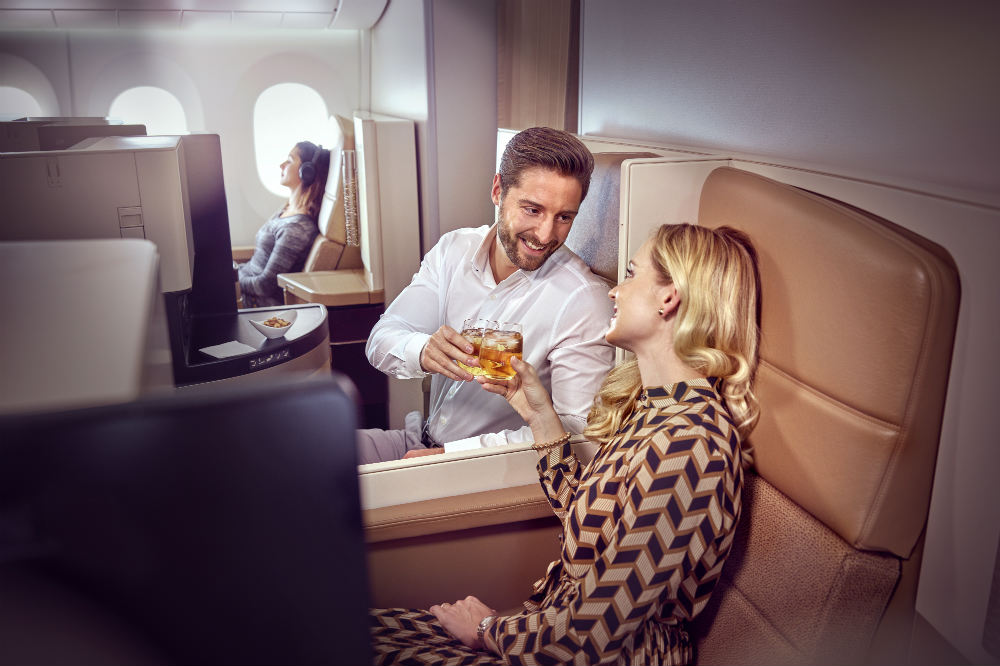 2 passengers enjoy a drink in a Etihad Airways Business Class cabin