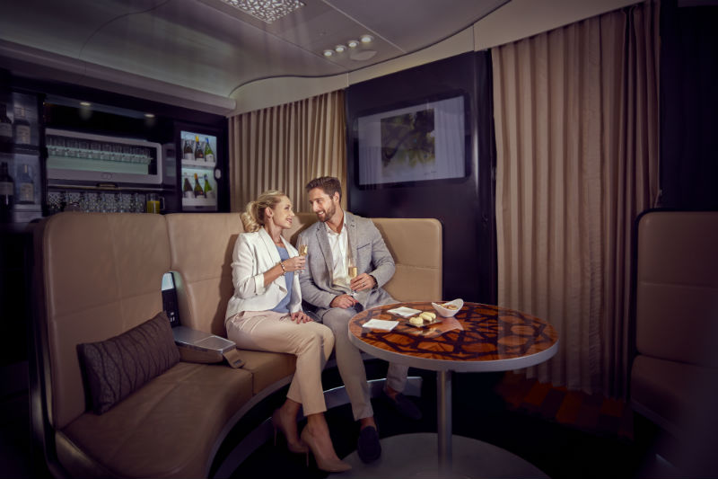 Etihad business class on board lounge area with 2 people enjoying a glass of champagne