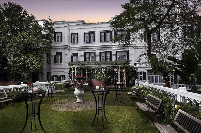 Exterior of Sofitel Legend Metropole in Hanoi Vietnam with tables and chairs in outdoor garden