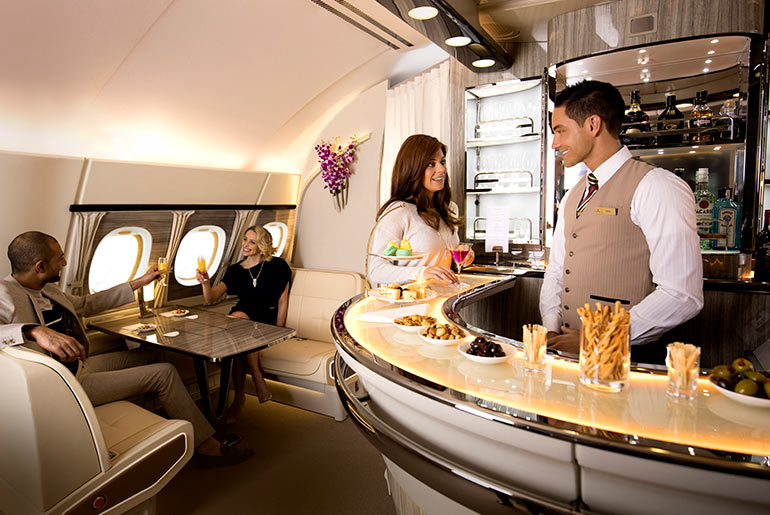 Woman being served in the onboard bar on the Emirates A380 Business Class cabin