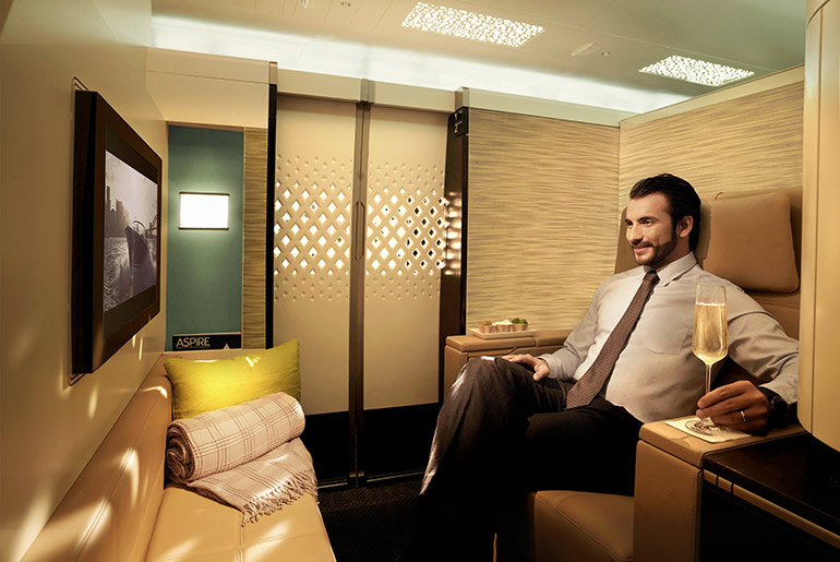 Etihad Airways First Class suite with man drinking champagne