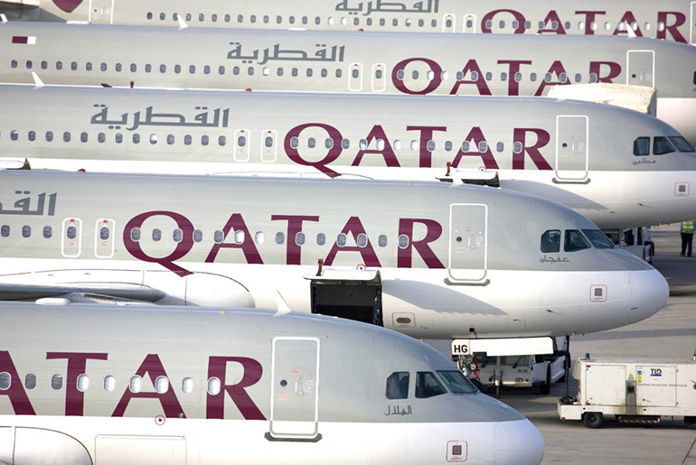 Qatar Airways planes lined up at an airport. These all have business and first class cabins