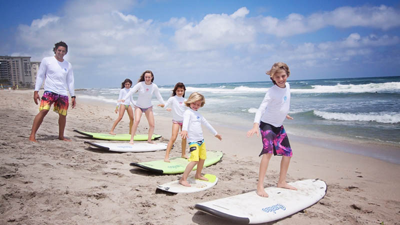 Children practicing surfing on the beach at Boca Beach Club in Palm Beaches