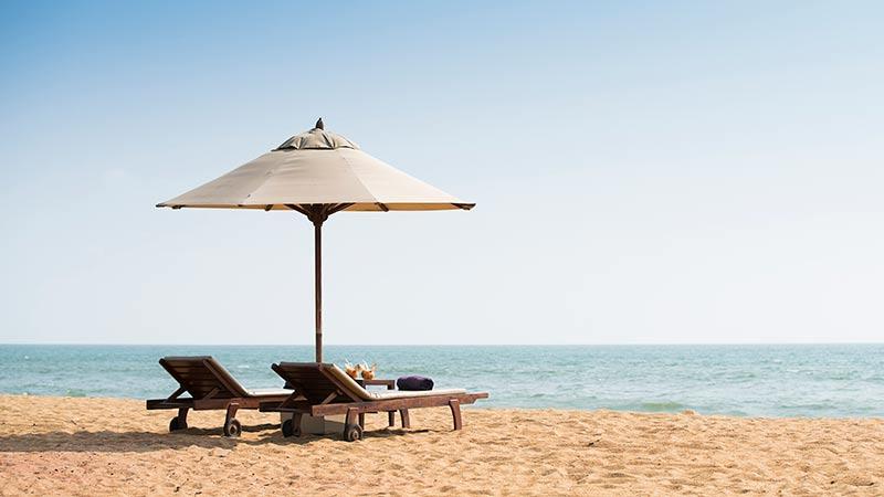 Beach view with parasol and loungers at Avani Kalutara Resort, Sri Lanka