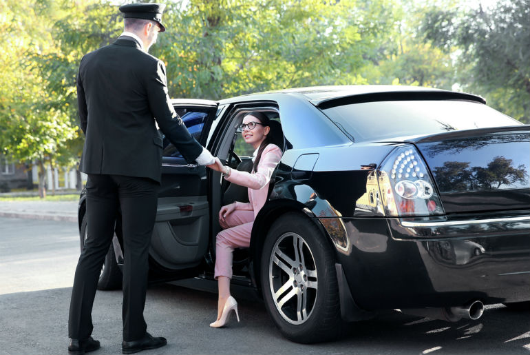 chauffeur opening car door for a woman - first class ground facilities