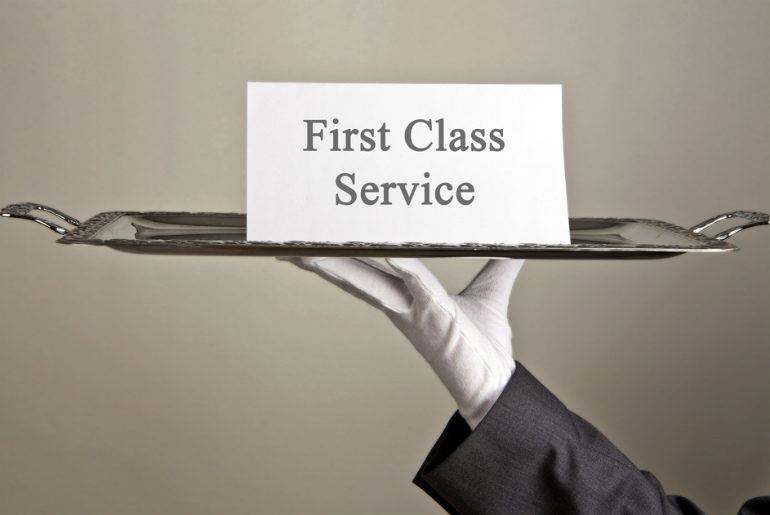 Sign saying First Class Service on a silver tray held by a gloved butler's hand