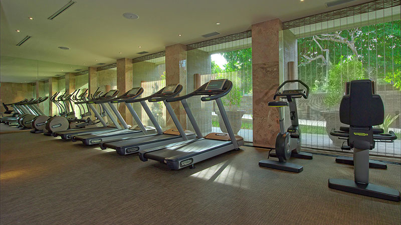 Treadmills with views out to tropical gardens in the fitness centre at Fairmont Sanur Beach Hotel in Bali
