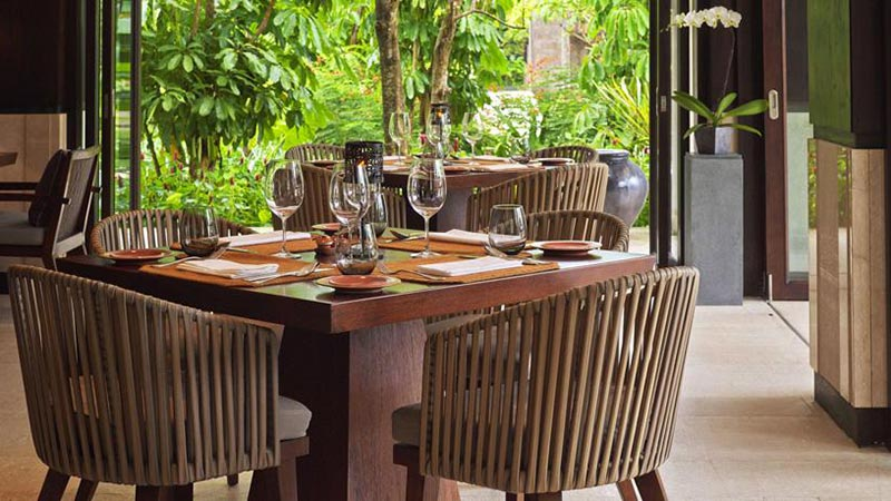 Wooden table set for dinner on an outdoor terrace at Fairmont Sanur Beach Hotel in Bali