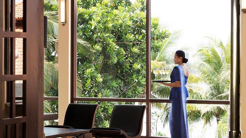 Woman carrying glasses at Avani Kalutara Resort, Sri Lanka