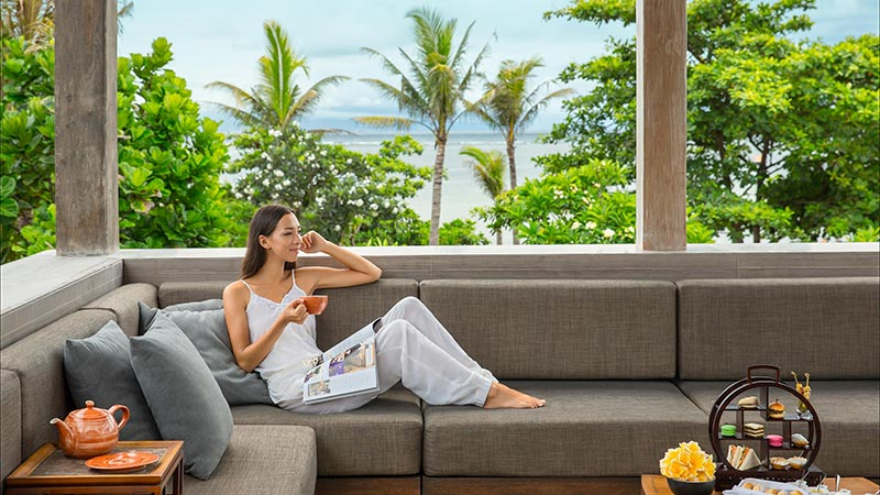 Lady drinking tea while lounging on an outdoor sofa overlooking the beach at Fairmont Sanur Beach Hotel in Bali