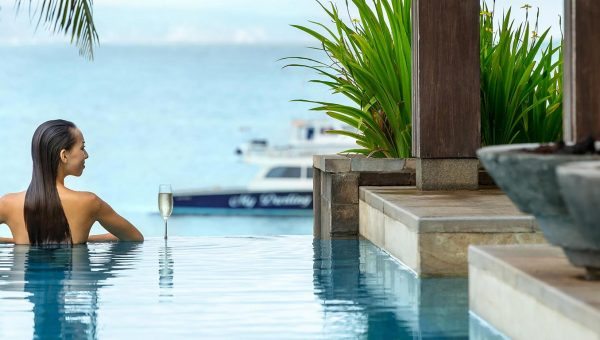 Woman at the edge of an infinity pool overlooking the ocean at Fairmont Sanur Beach Hotel Bali