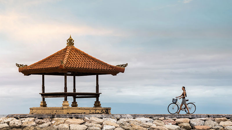 Lady riding a bicycle towards an Asian style hut at Fairmont Sanur Beach Hotel in Bali