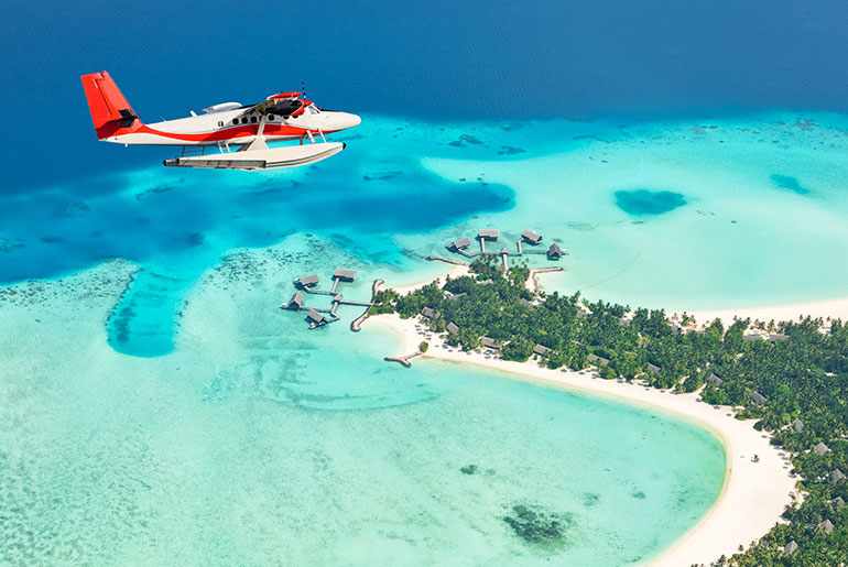 Seaplane Flying Over the Maldives with clear blue seas and over water villasr