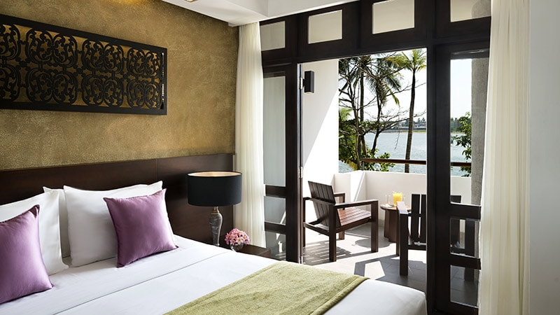 Double bed looking out to a furnished balcany with sea views at the Avani Kalutara Resort in Sri Lanka