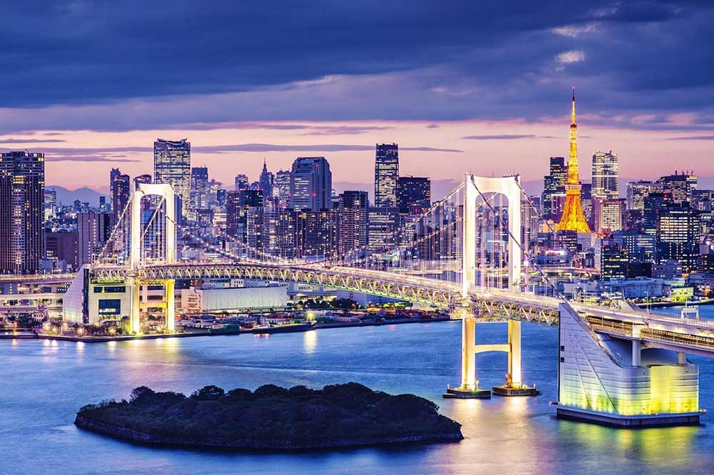 The Rainbow Bridge at night in Tokyo Japan with the Tokyo Tower and city skyline in the background