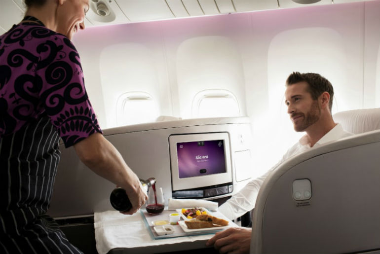 Cabin crew serving a man red wine while he enjoys a meal on Air New Zealand Business Premier