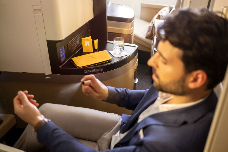 A business Class guest with a Acqua di Parma amenity kit, Etihad