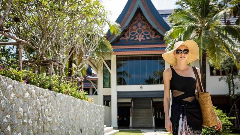 Woman walking outside the hotel at Outrigger Laguna Phuket, Thailand