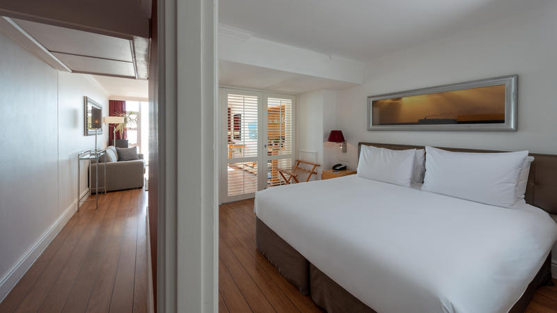Double bed in a family room with shutters leading to a lounge area and furnished balcony at the Radisson Blu Hotel Waterfront in Cape Town