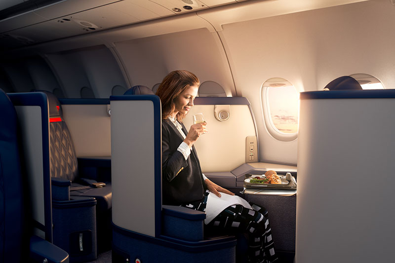 Woman dining on an in flight meal in Delta One Business Class