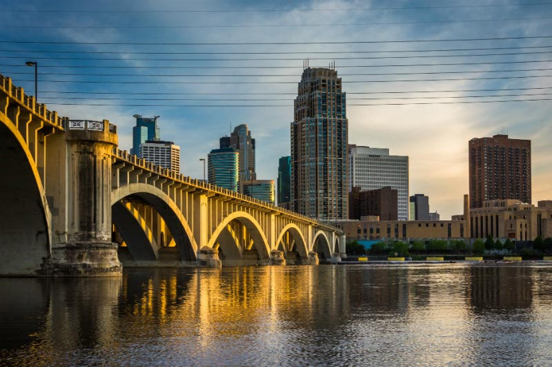 Stone Arch Bridge with the Minneapolis skyline behind. Fly to Minneapolis in business class on a direct flight with Delta Air Lines