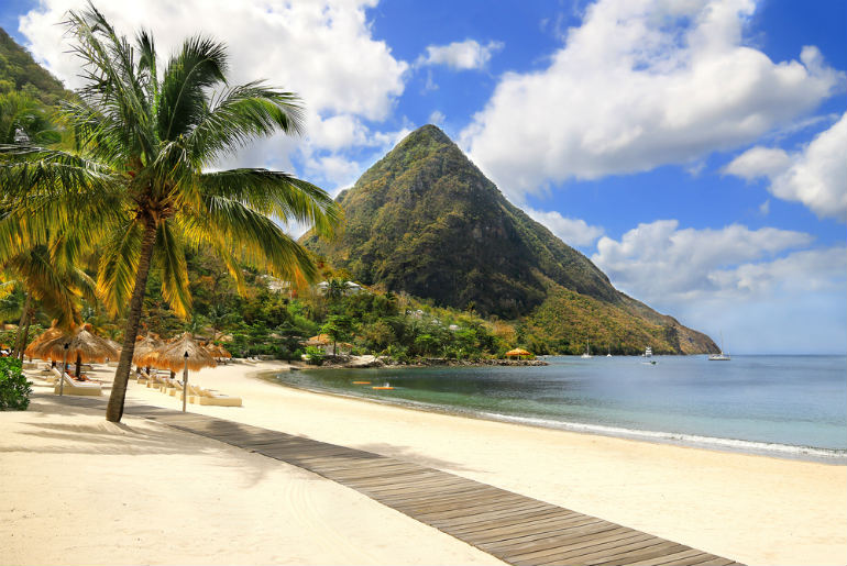 Boardwalk along a sandy beach with palm trees and sun lounges with a view of the Pitons of Saint Lucia