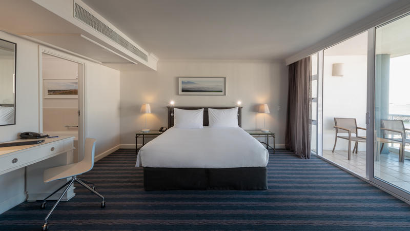 Double bed in a superior room with glass sliding door leading to a furnished balcony at the Radisson Blu Hotel Waterfront in Cape Town