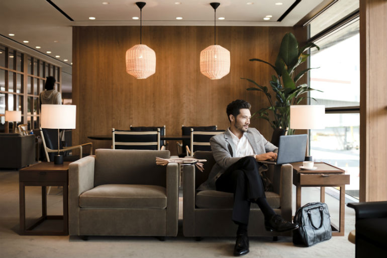 Gentleman sitting relaxing in The Pier, The Business Lounge Cathay Pacific