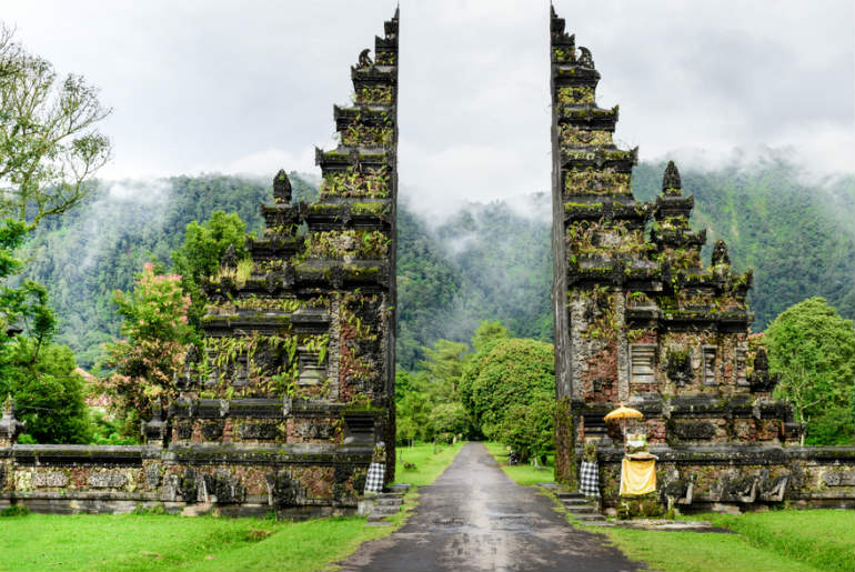 Large temple gates that lead to lush green forest