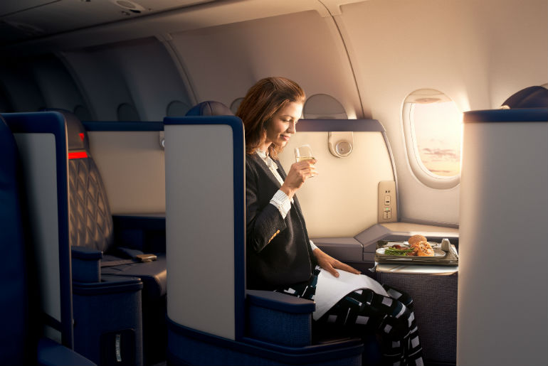 A lady sitting in Delta One business class seat enjoying a meal and a drink