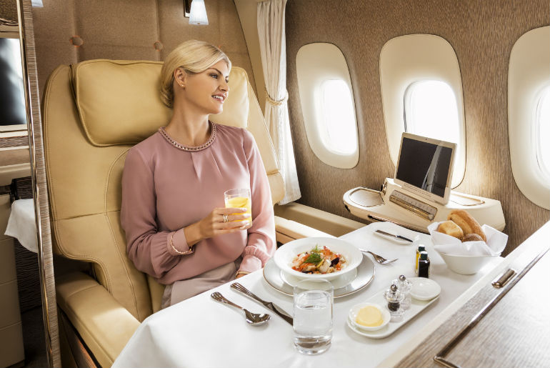 Lady enjoying Emirates in-flight First class dining experience