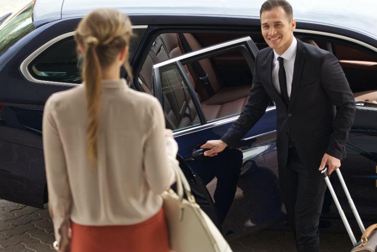 Emirates chauffeur assisting a customer into a dark blue BMW car