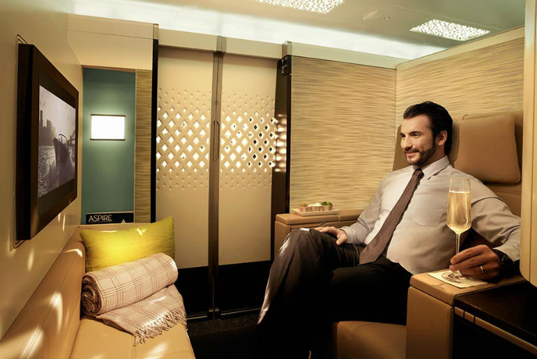 A man sitting in the first class etihad cabin enjoying a glass of champagne