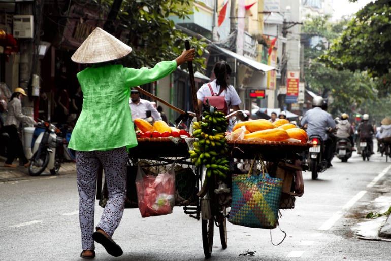 Hanoi busy streets, a lady riding a bike carrying food