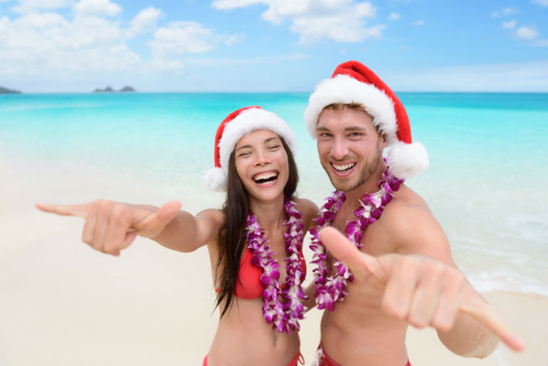 A couple on the Honolulu beach wearing Santa hats and Lei's