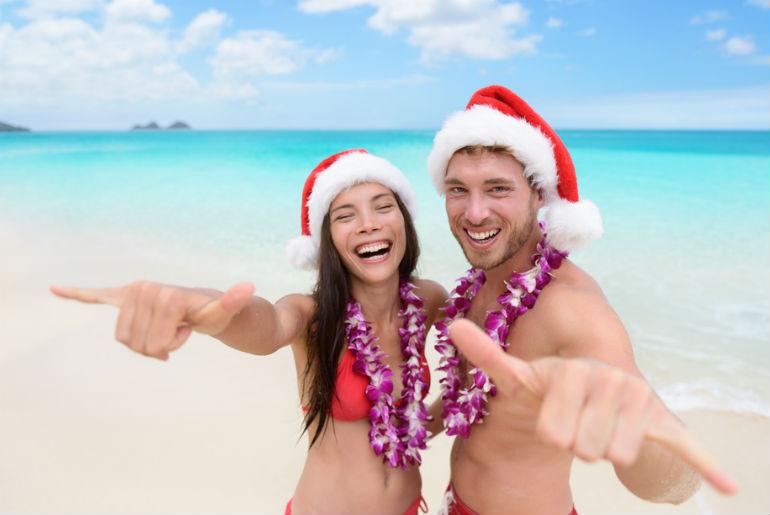 A couple on the Honolulu beach wearing Santa hats and Lei's