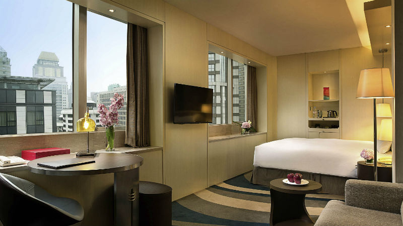 Junior Suite at the Sofitel Shanghai Hyland with a sofa and double windows over looking the city